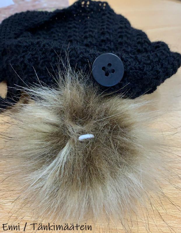 Myssyn sisäpuolella on nappi, johon tupsun saa kiinni tupsussa valmiina olevasta kuminauhalenkistä. Näin tupsun saa irrotettua esimerkiksi pesun ajaksi.